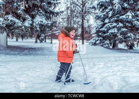 Little boy 3-4 years old, winter children's skis, happy smiling plays, having fun, active image of children. Background snow drifts trees. Free space - Stock Photo