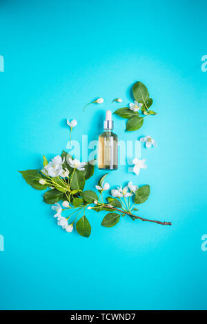 Natural organic cosmetics on a blue background in a frame of flowers, blossoming branches of an apple tree. Spring skin care. - Stock Photo
