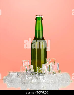 Beer bottle in ice on red background - Stock Photo