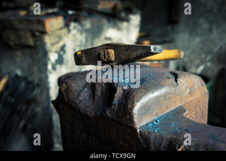 hammer and anvil in smithy - Stock Photo
