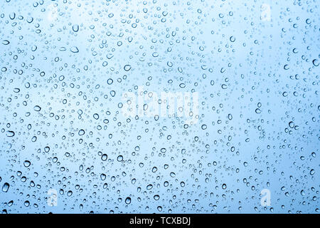 Close up view of water drops falling on glass. Rain running down on window. Rainy season, autumn. Raindrops trickle down, grey sky. - Stock Photo