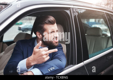 Rude businessman. Angry and rude bearded businessman in formal wear is gesturing and making a grimace while driving his car. Negative emotions. Busine - Stock Photo