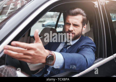 I don't like it. Angry and emotional businessman in formal wear is gesturing and making a grimace while driving his car. Negative emotions. Business c - Stock Photo