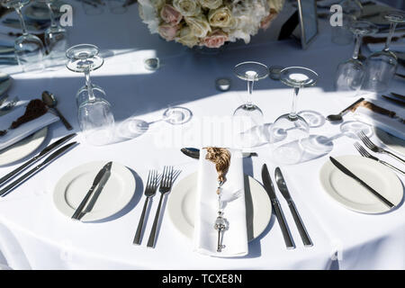 Well-maintained table for celebrating the apple tree on the Greek seashore by the sea. Preparation for the celebration - Stock Photo