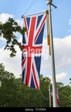 Union Jack flag flying from a roadside flagpole in The Mall, London, UK in spring with green trees and blue sky - Stock Photo