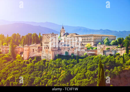 Amazing Alhambra palace complex taken in the morning in sunrise light. Beautiful piece of Moorish architecture, surrounded by green trees, is located in Granada, Spain. - Stock Photo