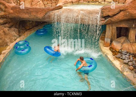 Orlando, Florida. April 07, 2019. Man and boy floating at Lazy River in Aquatica water park . - Stock Photo