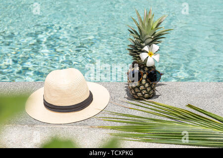 Funny pineapple with sunglasses and flower and hat by swimming pool. - Stock Photo