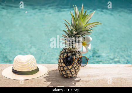 Funny pineapple in sunglasses with plumeria flower and hat near swimming pool. - Stock Photo