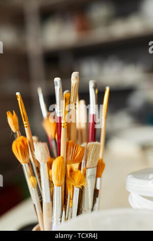 Close up of paintbrushes on table in art studio, copy space Stock Photo