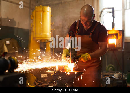 Frowning bald blacksmith in apron cutting heated metal piece with grinder on anvil while working in smithy - Stock Photo