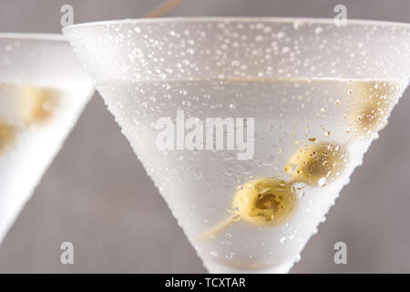 Classic Dry Martini with olives on wooden table - Stock Photo