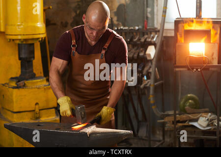 Focused young man in leather apron and protective gloves standing at anvil and beating hot iron with hammer - Stock Photo