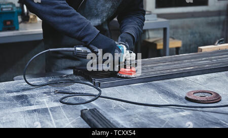 Worker, wearing special protective gloves, using grinder to polish piece of metal frame pressed to work table. Man holding hand grinder. Close up. Hor - Stock Photo