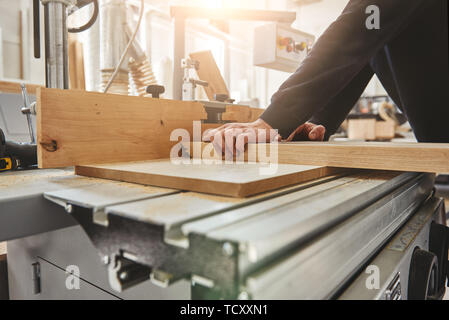 Close up of circular saw for cutting boards and the hands of the builder holding wood plank. The man sawed bars, construction and home renovation, rep - Stock Photo
