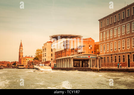 Venice Italy - May 25, 2019:  Panoramic view of Venice hospital alongf the grande canal at sunset with docks for emergency boats and helicopter deck. - Stock Photo