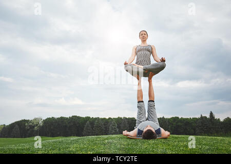 Find you balance, find yourself. Beautiful young couple doing acro yoga in nature. Strong man lying on a mat and balancing woman in lotus pose on his  - Stock Photo