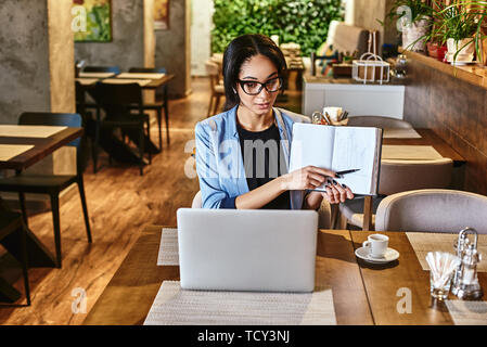 Positive stylish businesswoman in blue jacket and glasses sitting at the table, indoors, wearing wireless earbuds, chatting with her boss via video co - Stock Photo