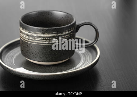 Gray cup and saucer on a black table. Close up with shallow depth of field - Stock Photo