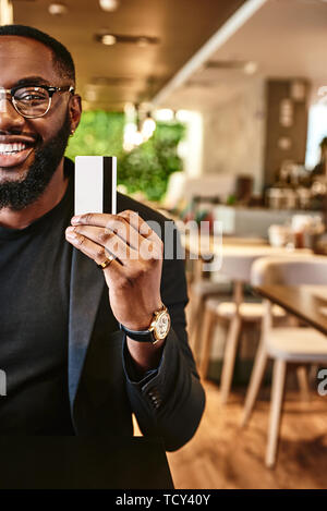 Cropped shot of African-American male in dark-blue jacket and glasses, holding credit card. He is going to make a transaction. Online payment and shop - Stock Photo