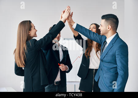 Smiling young business people giving high five to each other in office. Business success concept - Stock Photo