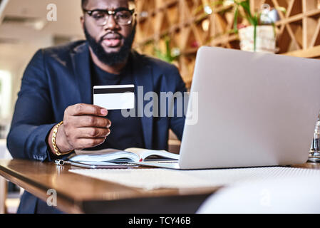 Cropped shot of African-American male holding credit card, making transaction. His working papers and laptop are on the table. Online payment and shop - Stock Photo