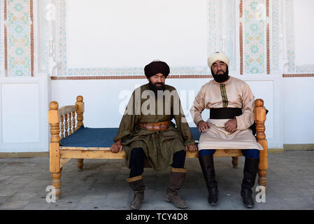 Kokand, Fergana Valley, Uzbekistan - 4 JUNE 2019: The Uzbek men, dressed into into the traditional turban, sitting on the bench in the Palace of Khuda - Stock Photo