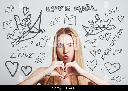 Valentines Day. Romantic young woman making heart shape and rounded lips while standing against grey background with doodles on the theme of St.Valent - Stock Photo