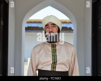 Kokand, Fergana Valley, Uzbekistan - 4 JUNE 2019: Portrait of the Uzbek man, dressed into into the traditional turban,  standing in the door of the Pa - Stock Photo