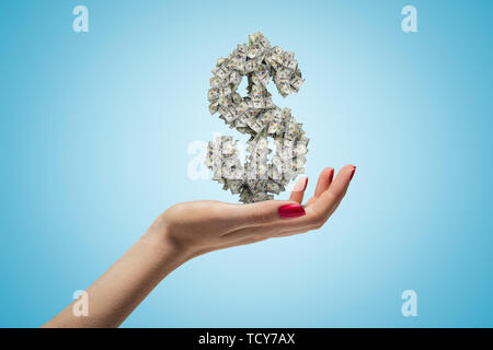 Female hand holding dollar sign on blue background - Stock Photo