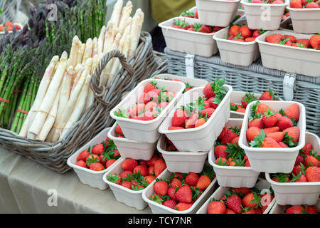 Fragaria × ananassa. Punnets of fresh strawberries and asparagus for sale at Daylesford Organic farm summer festival. Daylesford, Cotswolds, UK - Stock Photo