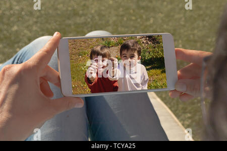 Human hands holding mobile looking at a picture of two twin children. - Stock Photo