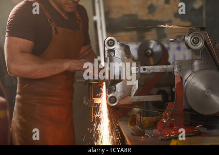 Busy blacksmith in leather apron adjusting detail on flat grinding machine while shaping it in workshop - Stock Photo