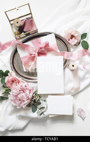Feminine vertical wedding, birthday mock-up scene. Blank paper greeting cards, eucalyptus, pink roses, peony flowers on white table background.Golden - Stock Photo