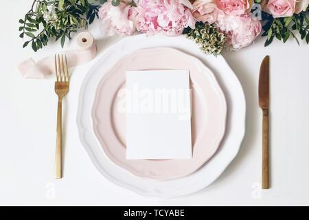 Feminine wedding, birthday desktop mock-up scene. Porcelain plates, blank paper greeting, menu card, ribbon, golden cutlery, leaves,roses, peony - Stock Photo