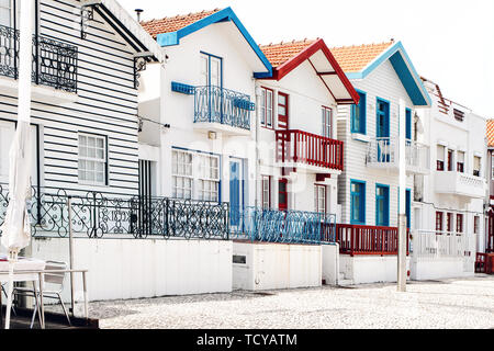 Street with colorful striped houses in Costa Nova village, Aveiro, Portugal. Famous resort on the Atlantic coast in Beira Litoral. Popular tourist - Stock Photo