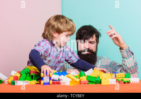 happy little boy with bearded man dad playing together. father and son play game. building home with colorful constructor. happy child development. happy family. leisure time. feeling happy. - Stock Photo