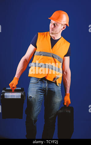 Handyman, repairman on strict face goes and carries bags with professional equipment. Man in helmet, hard hat holds toolbox and suitcase with tools, blue background. Professional repairman concept. - Stock Photo