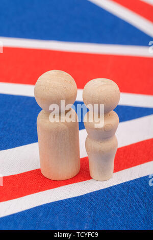 Small wooden abstract figures on Union Jack flag - representing demographic of UK family life / family unit. - Stock Photo