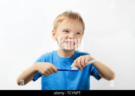A happy six year old boy squeezes toothpaste onto a toothbrush. Dental hygiene concept - Stock Photo