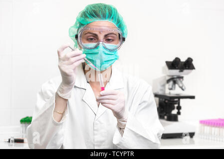 Young attractive concentrated female scientist in protective eyeglasses, mask and gloves dropping a red liquid substance into the test tube with a pipette in the laboratory .