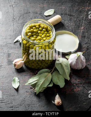 Open glass jar with green peas. On dark rustic background - Stock Photo