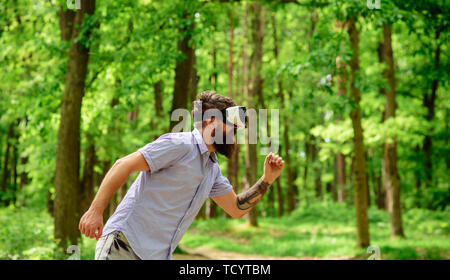 handsome man wearing virtual reality headset in city park - Stock Photo