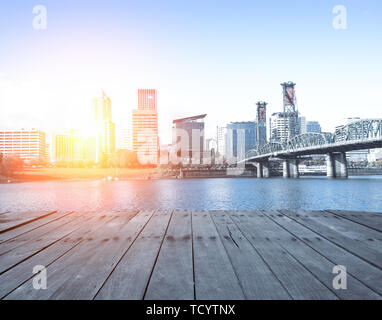 empty wood floor near steel bridge over water with cityscape and skyline of portland at sunrise - Stock Photo