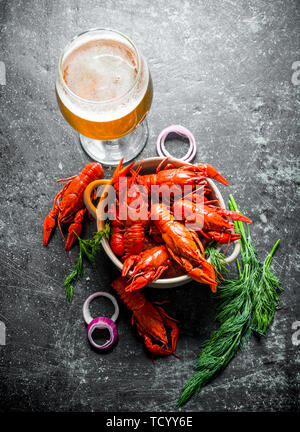 Fragrant boiled crayfish in a bowl with beer, dill and onion rings. On dark rustic background - Stock Photo