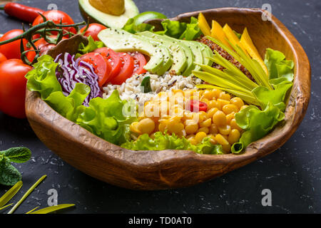 Healthy vegan superfood bowl with quinoa, wild rice, chickpea, tomatoes, avocado, greens, cabbage, lettuce on black stone background - Stock Photo