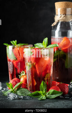 Fresh lemonade with ice, mint and strawberry on top in glass on black table background. Cold summer drink. Sparkling glasses with berry cocktail - Stock Photo