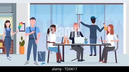 janitors team cleaners in uniform working together with professional equipment cleaning service concept creative co-working center modern office - Stock Photo
