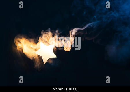 Star flare, a shining star from paper on a dark background with gradient warm and cold smoke. Celebration concept with copy space - Stock Photo