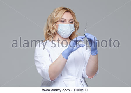 Female doctor in face mask holding syringe. Portrait of young woman doctor or nurse in protective gloves holding an injection - Stock Photo